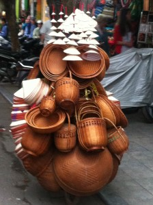A man selling hats and baskets from the back of his bike in Hanoi